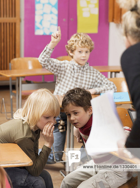 Boy (4-7) raising hand in classroom  focus on boys whispering in foreground