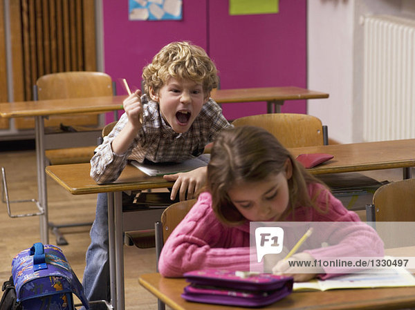Boy (4-7) shouting behind girl in class room