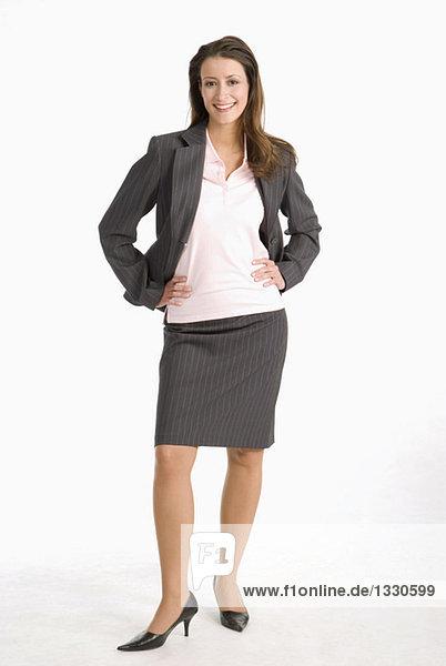Geschäftsfrau stehend mit den Händen auf der Hüfte  lächelnd  Portrait