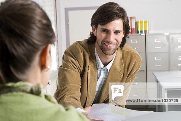 Geschäftskollege im Büro  Mann übergibt Dokument an Frau  lächelnd