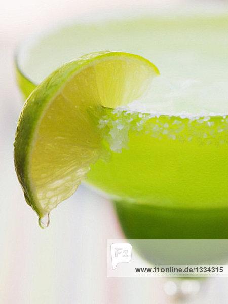 Limettenspalte an Cocktailglas mit Zuckerrand Limettenspalte an Cocktailglas mit Zuckerrand