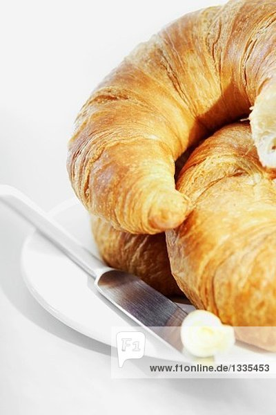 Croissants auf einem Teller mit Messer und Butter