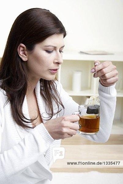 Frau nimmt Teebeutel aus dem Tee