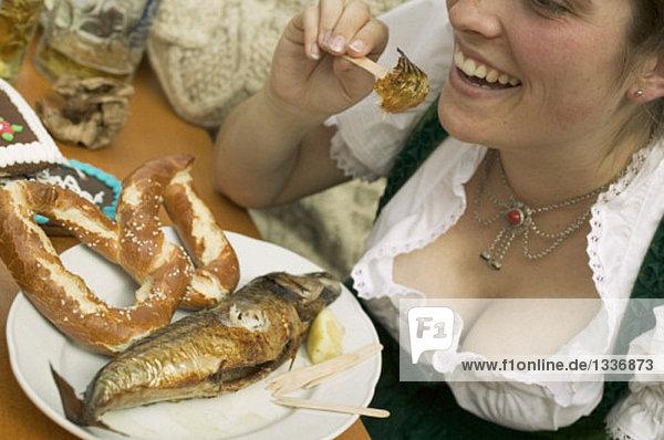 Frau isst Steckerlfisch mit Brezel beim Oktoberfest