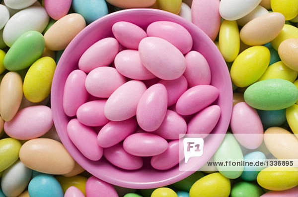 Sugared almonds  in and around pink bowl