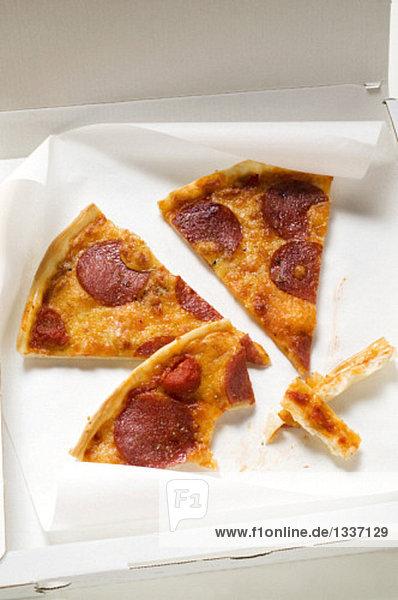 Drei Stücke Pizza mit Peperoniwurst im Pizzakarton