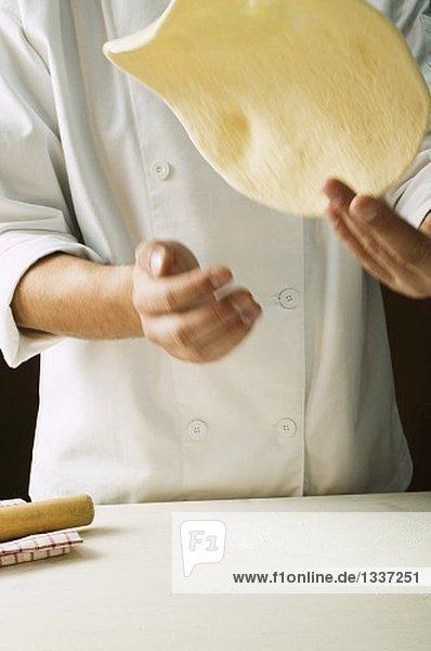 Pizzateig formen (in die Luft werfen) Pizzateig formen (in die Luft werfen)
