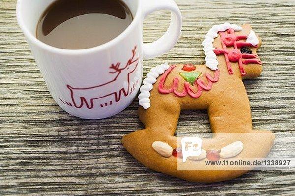 Lebkuchenschaukelpferd und Tasse Kakao Lebkuchenschaukelpferd und Tasse Kakao