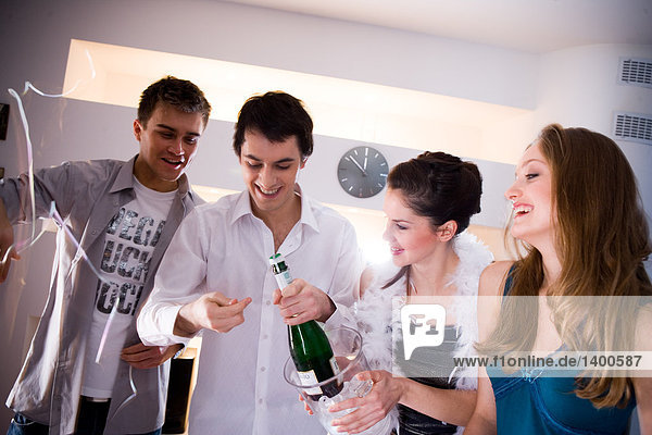 friends opening champagne