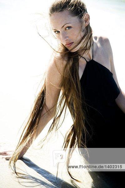 Frau Schönheit im schwarzen Kleid am Strand