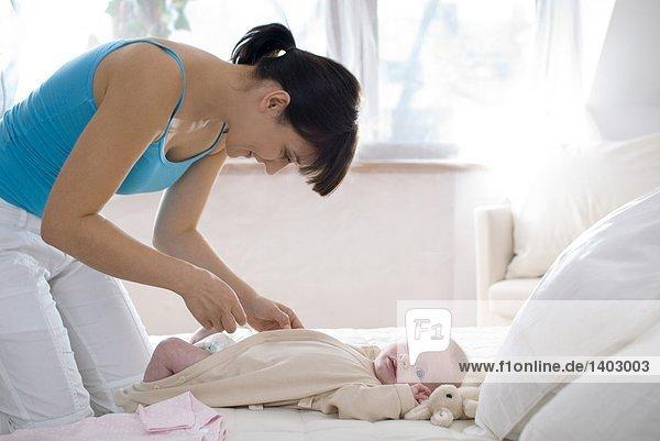 mum dressing infant