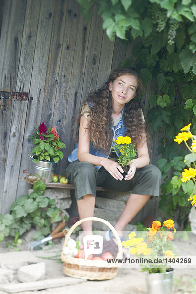 junge Frau im Garten hält Korb mit Gemüse