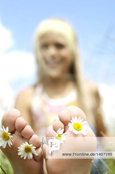 Mädchen mit Blumen in ihren Füßen