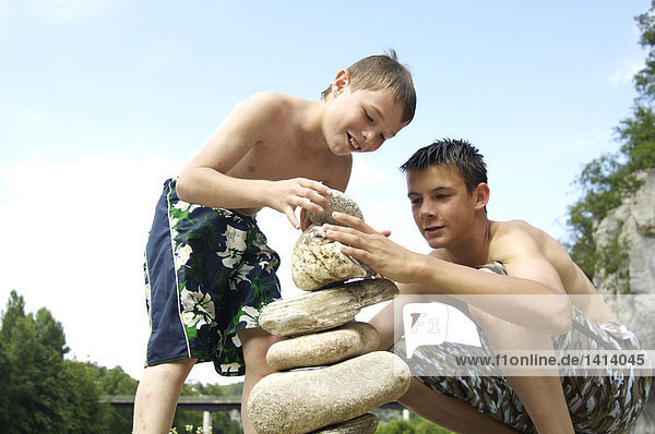 Two boys making stone pyramid at riverside  Ardeche  France