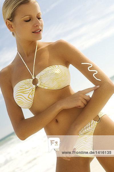 Junge Frau im Bikini am Strand mit Sonnencreme