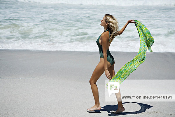 Young woman in swimming costume  walking on the beach
