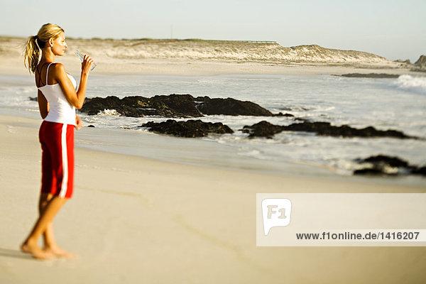 Junge Frau steht am Strand und trinkt Wasser aus einer Flasche.