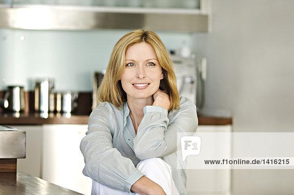 Lächelnde Frau in der Küche sitzend