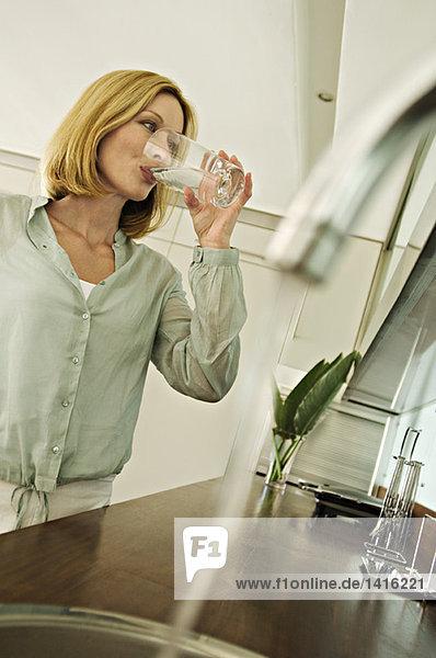 Frau trinkt ein Glas Wasser  Wasserhahn im Vordergrund