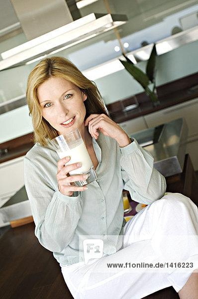 Frau hält ein Glas Milch in der Hand