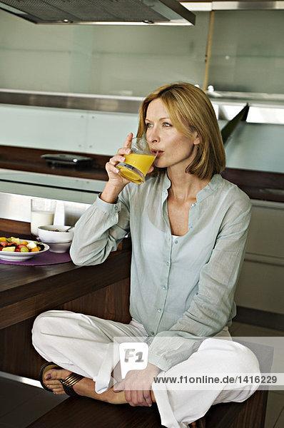 Frau trinkt Fruchtsaft  im Schneidersitz