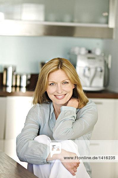 Frau lächelt für die Kamera in der Küche