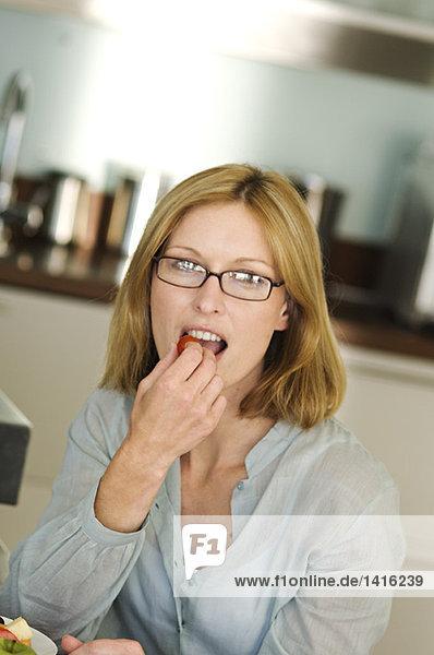 Frau isst Kirsch-Tomate
