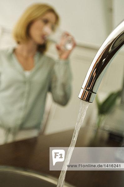 Frau Trinkwasser  Wasserhahn im Vordergrund