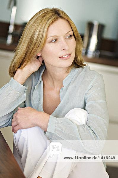 Denkende Frau  sitzend in der Küche