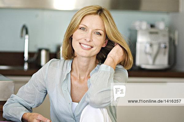 Lächelnde Frau mit Hand im Haar