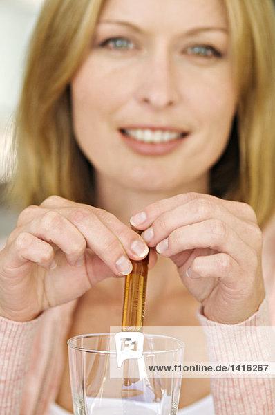 Frau zerbricht Ampulle in einem Glas