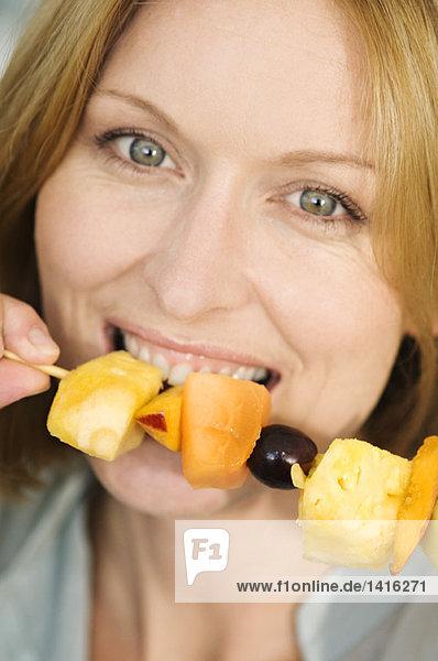 Porträt einer Frau  die Obstspieß isst