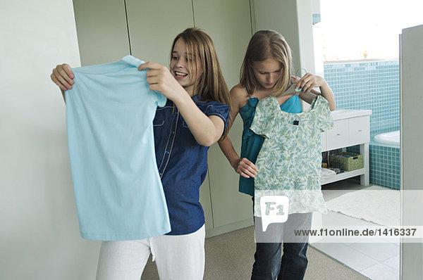 2 Teenager-Mädchen beim Anprobieren von Kleidung
