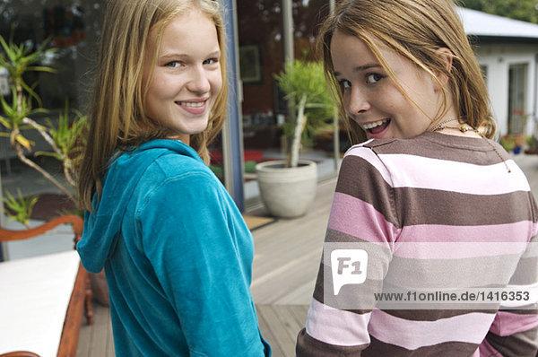 2 lächelnde Teenagermädchen  die über die Schultern schauen