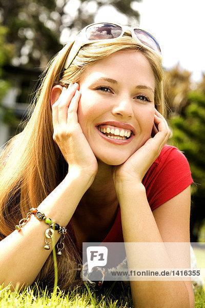 Junge lächelnde Frau auf Gras liegend