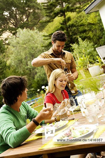 2 junge Männer und eine Frau am Gartentisch  Mann öffnet Weinflasche
