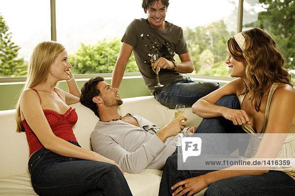 2 junge lächelnde Paare  die Champagner trinken  auf dem Sofa sitzend