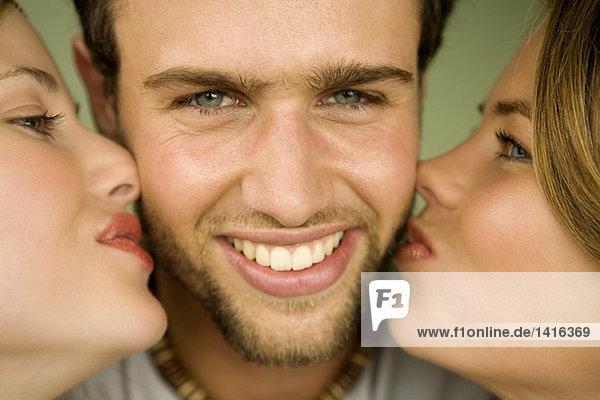 2 junge Frauen küssen lächelnden Mann