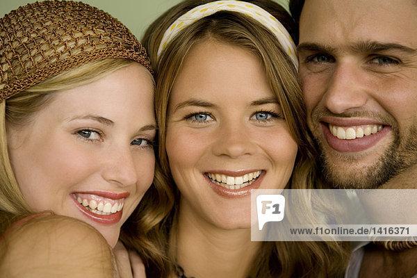Porträt von 2 Frauen und einem Mann  der für die Kamera lächelt