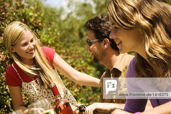 2 junge Frauen und ein Mann sitzen am Gartentisch
