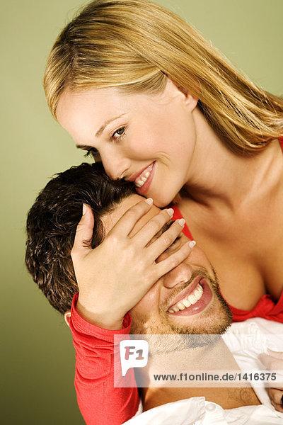 Junge lächelnde Frau mit Hand über den Augen des Mannes