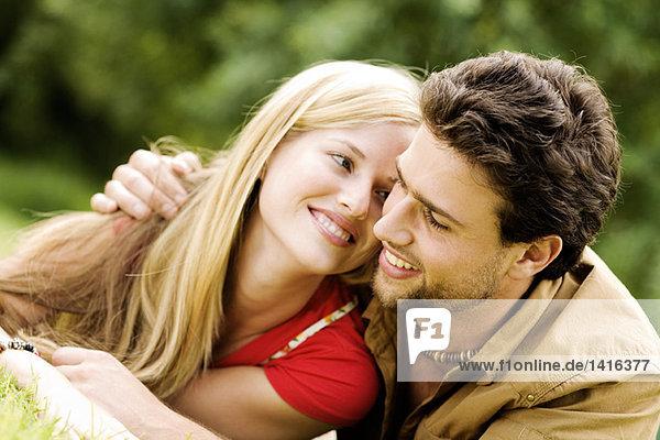 Porträt eines jungen lächelnden Paares  das sich im Freien umarmt.