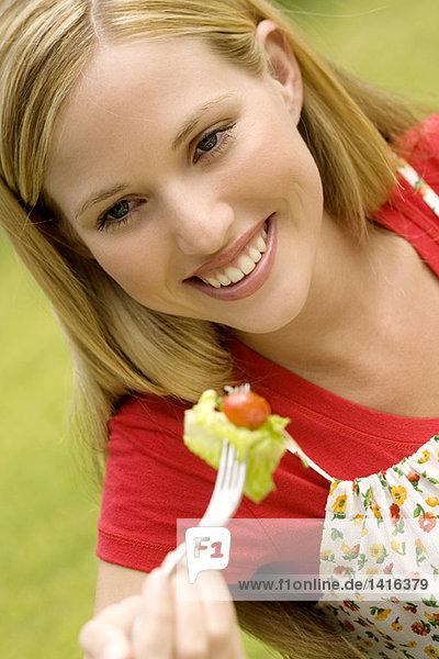 Porträt einer jungen lächelnden Frau beim Salatessen  im Freien