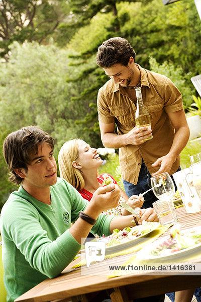 2 Männer und eine Frau sitzen am Gartentisch