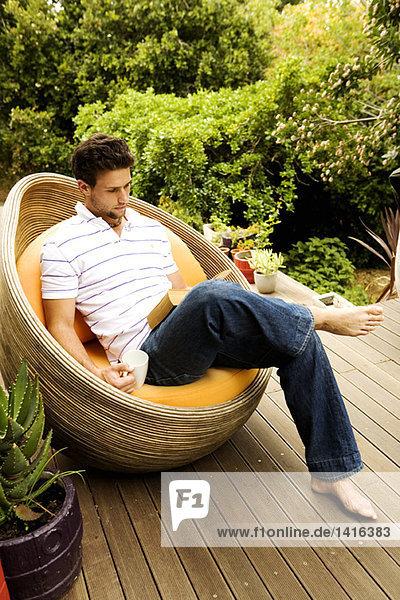 Junger Mann sitzt im Sessel und liest ein Buch.