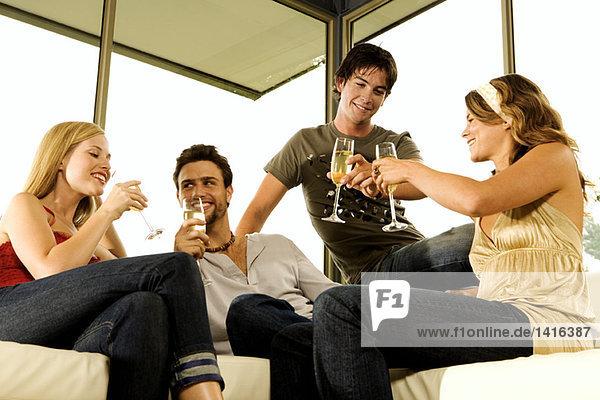 2 junge Paare trinken Champagner
