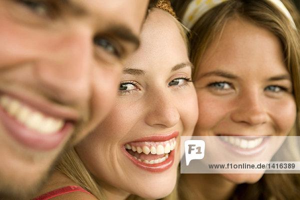 2 junge Frauen und ein Mann lächelnd für die Kamera