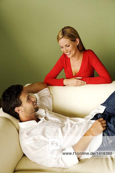 Junge Frau lächelt den Mann an  der auf dem Sofa liegt.