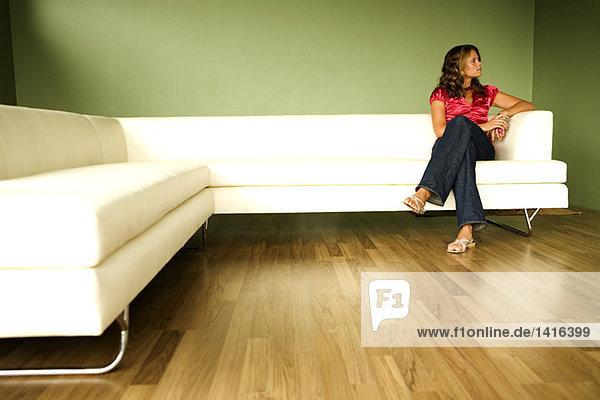 Junge Frau auf einem Sofa sitzend