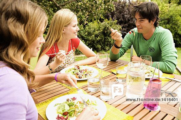 2 Frauen und ein Mann sitzen am Gartentisch